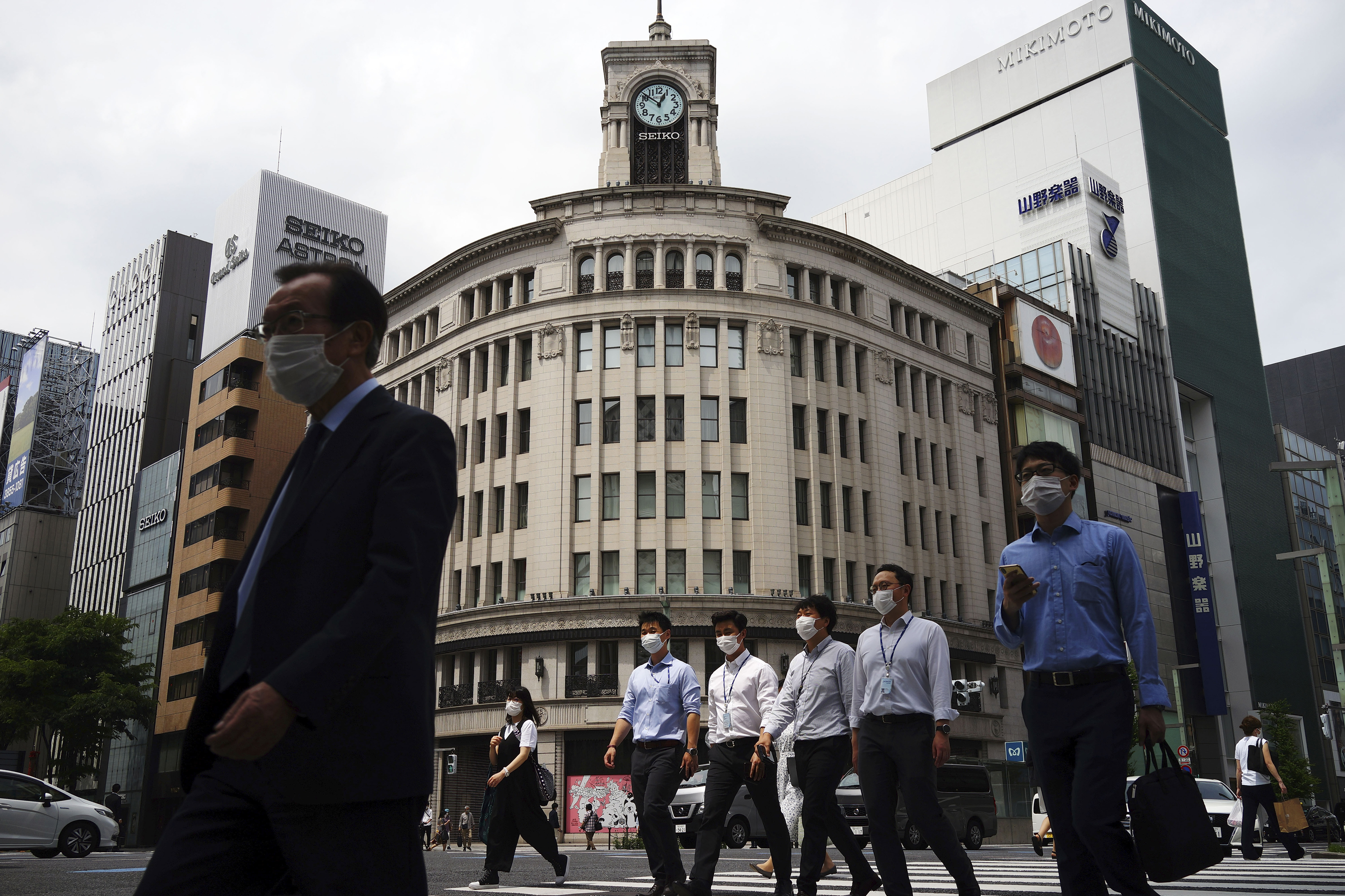 People wearing face masks to help curb the spread of the coronavirus walk at Ginza shopping district in Tokyo Tuesday, May 12, 2020. Japan is still under a coronavirus state of emergency which was extended until the end of May though there have been no hard lockdowns. (AP Photo/Eugene Hoshiko)