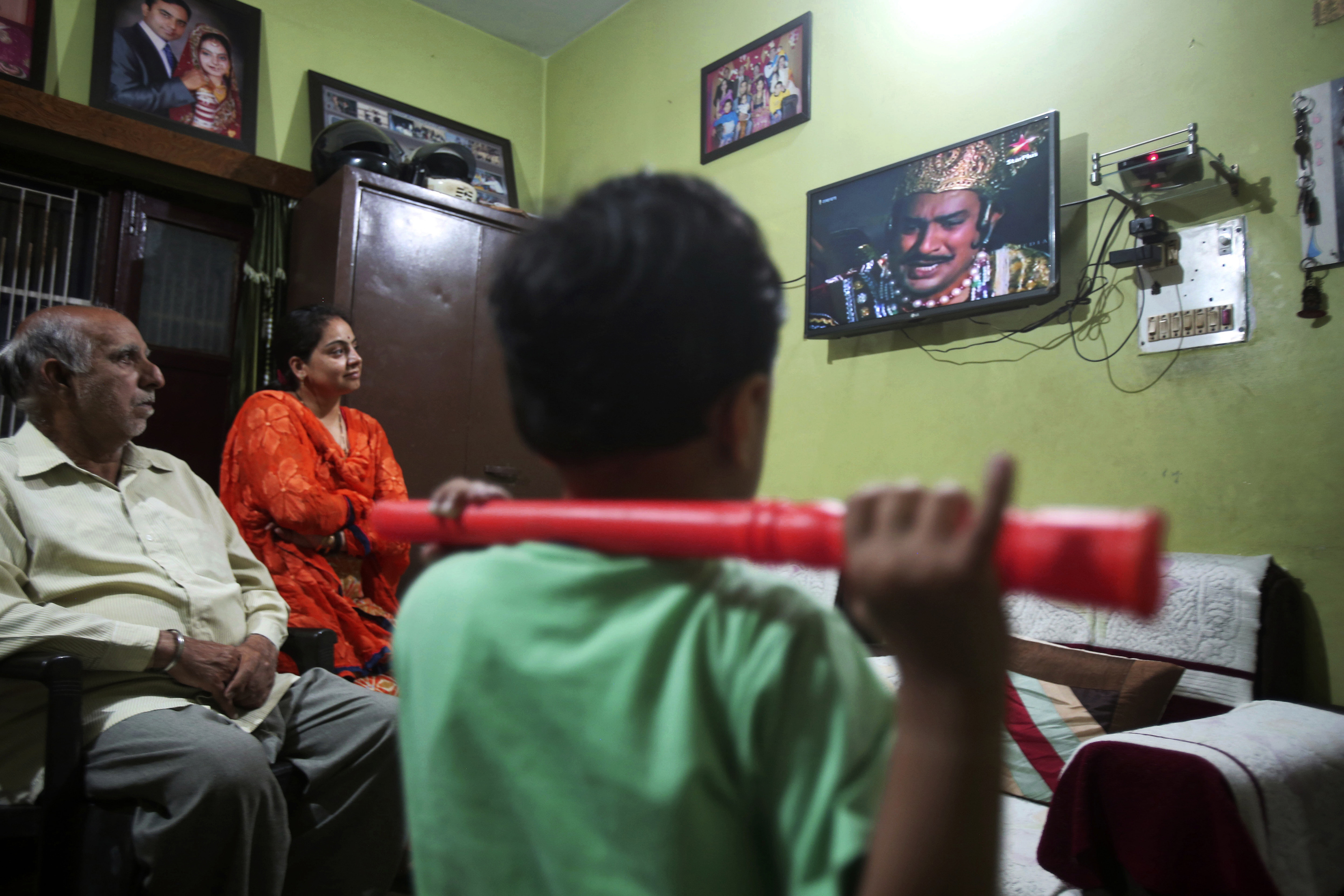 An Indian family watches epic television series u201cRamayanu201d at their home in Jammu, India May 18, 2020. The countryu2019s public broadcaster last month revived the wildly popular series from the 80s and brought back to life for a captive audience under lockdown. Staying home under a lockdown as they wait for the worst of the coronavirus pandemic to pass, millions of Indians are turning to their Gods. Not in their prayer rooms, but on their televisions. Photo: AP