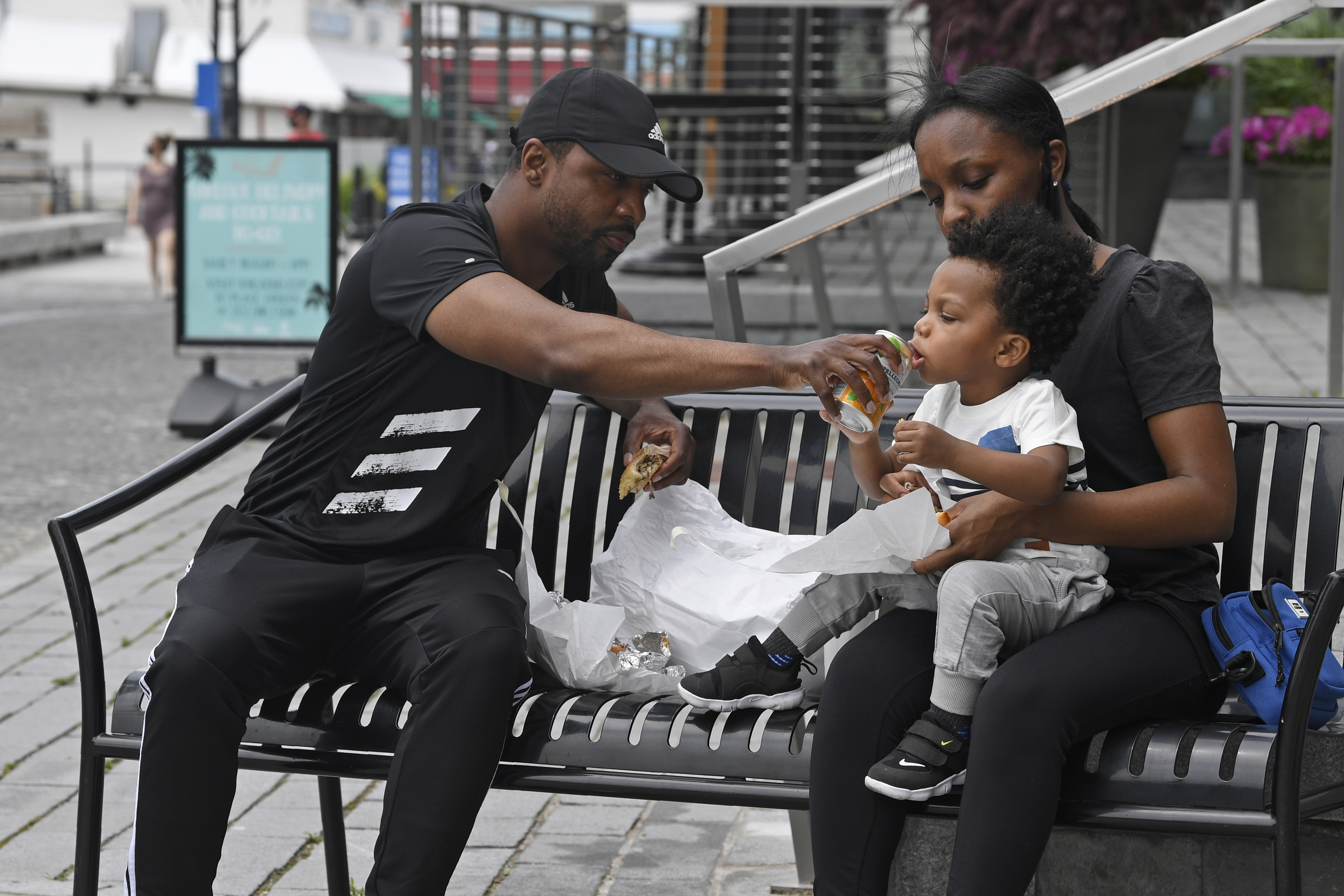 John Price and Bijan Black have lunch with their son Parker Price, 2, all of Seat Pleasant, Md., at the Wharf area in Washington, Friday, May 29, 2020. Photo: AP