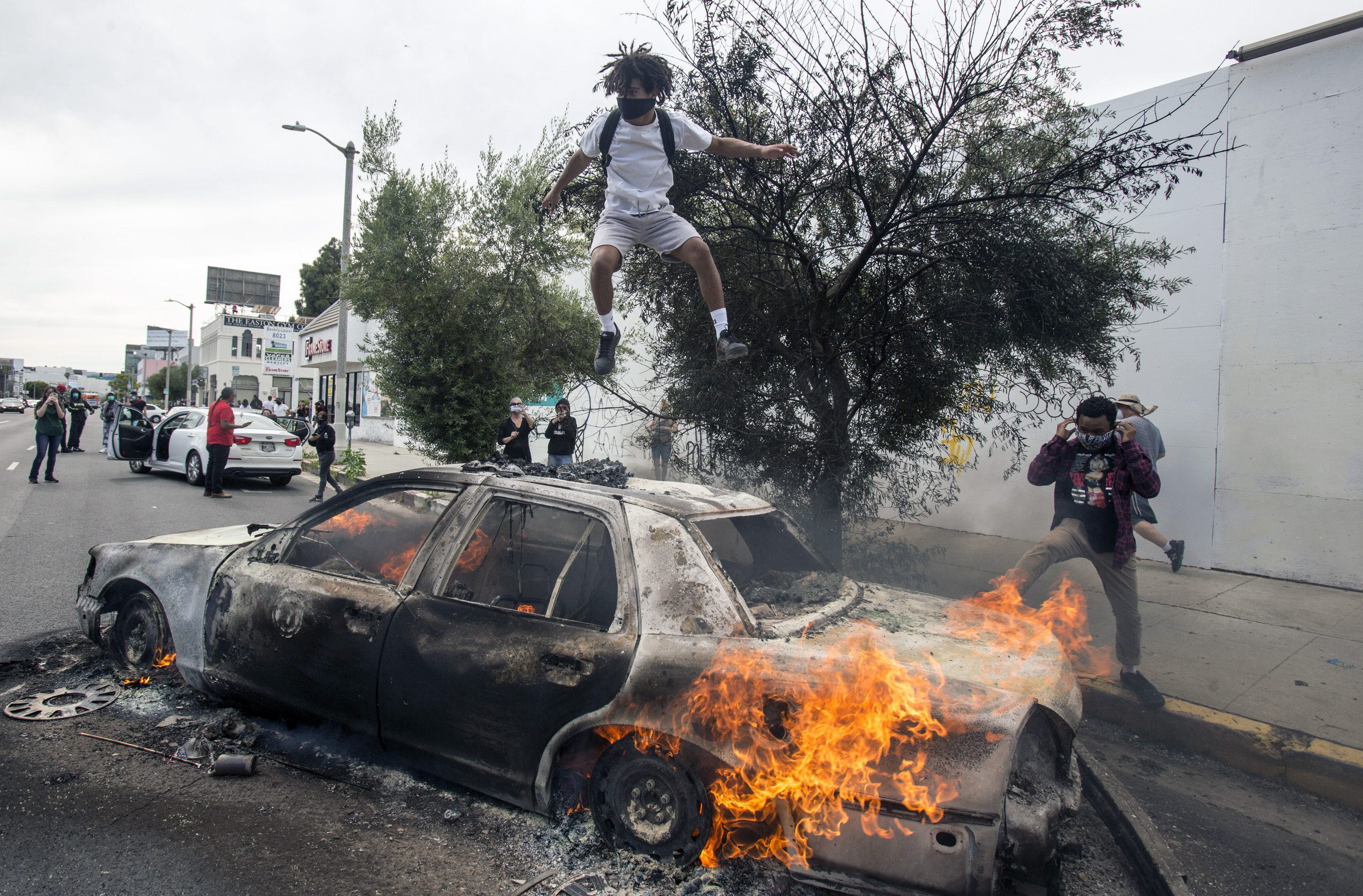 A person jumps on a burning police vehicle in Los Angeles, Saturday, May 30, 2020, during a protest over the death of George Floyd.Photo: AP