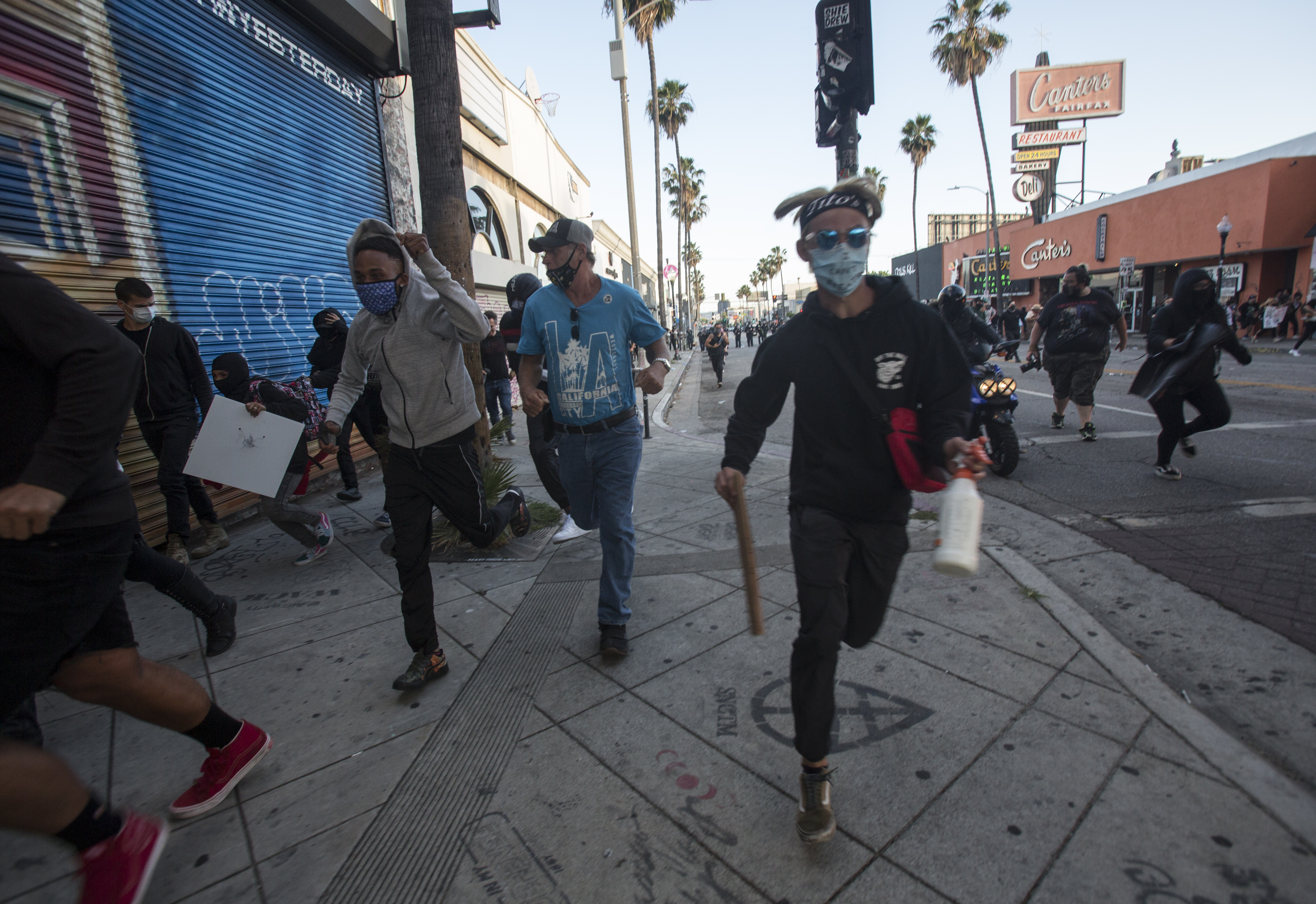Protesters run as police officers fire rubber bullets during a protest over the death of George Floyd, a handcuffed black man in police custody in Minneapolis, in Los Angeles, Saturday, May 30, 2020. Photo: AP