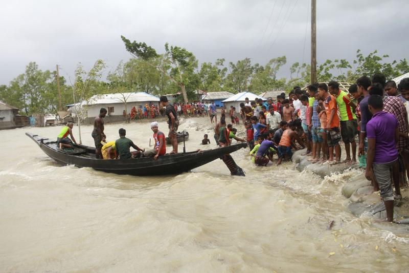 A boat brings people to land, as locals check an embankment before Cyclone Amphan made landfall, in Shyamnagar, Shatkhira, Bangladesh, Wednesday, May 20, 2020. Photo: AP