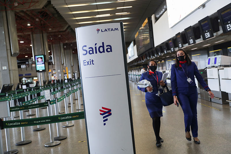 Latam Airlines employees walk at the company's check-in hall at Guarulhos International airport as air traffic is affected by the outbreak of the coronavirus disease (COVID-19), in Guarulhos, near Sao Paulo, Brazil, May 19, 2020. Photo: Reuters