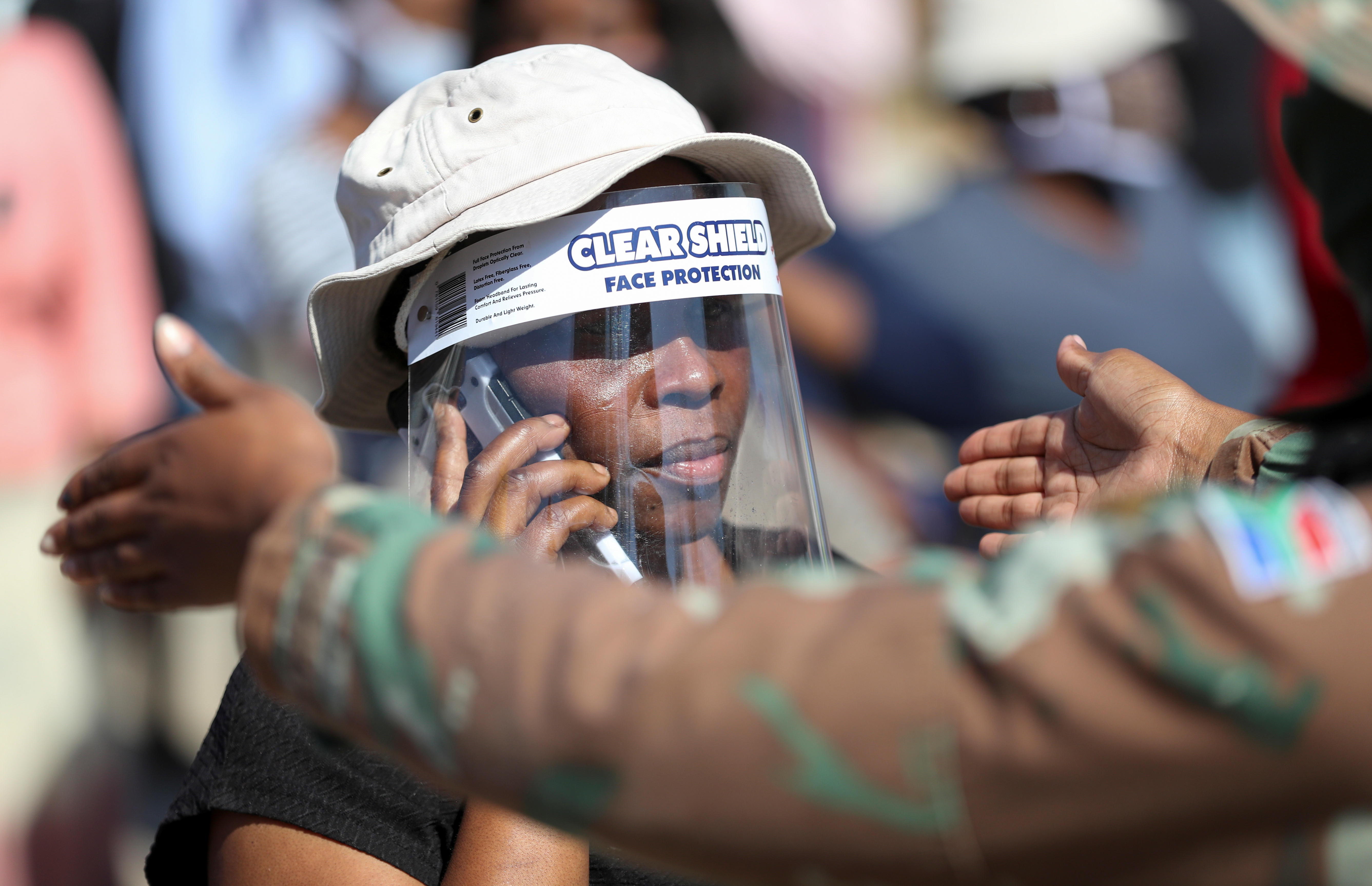 A woman wears a protective face shield during food distribution, as South Africa starts to relax some aspects of a stringent nationwide coronavirus disease (COVID-19) lockdown, in Diepsloot near Johannesburg, South Africa, May 8, 2020. Photo: Reuters