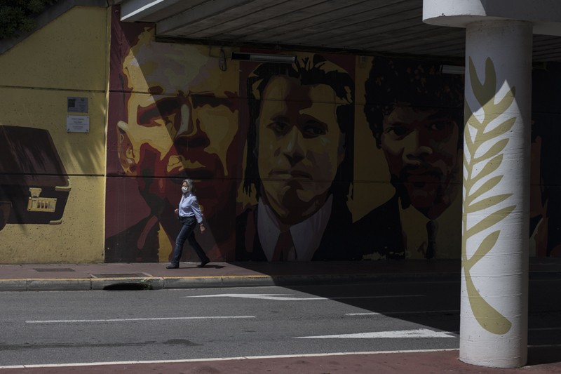 A woman wearing a face mask to protect against coronavirus walks by a mural depicting characters from the film Pulp Fiction in Cannes, southern France, Tuesday, May 12, 2020. Photo: AP
