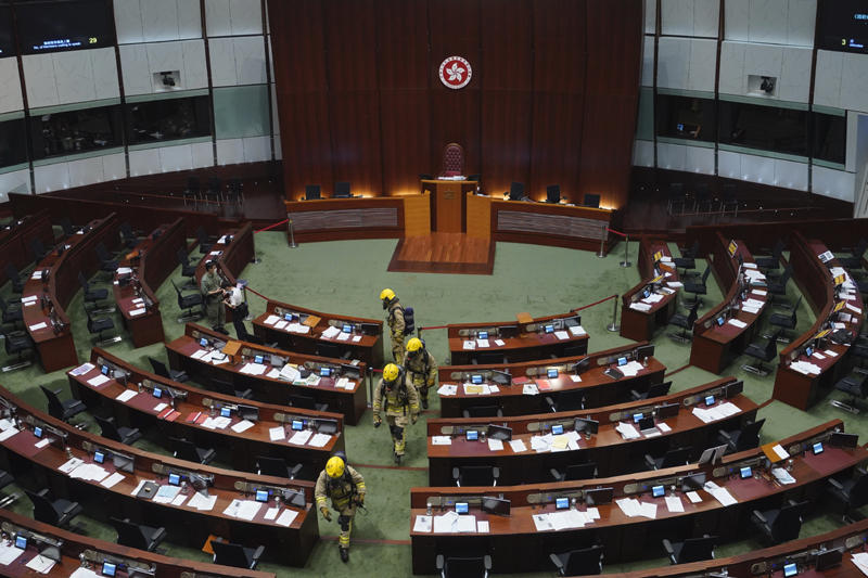 Firefighters wearing gas masks check the main chamber of the Legislative Council after a pro-democracy lawmaker hurled an object during the second day of debate on a bill that would criminalize insulting or abusing the Chinese anthem in Hong Kong, Thursday, May 28, 2020. Three pro-democracy lawmakers were ejected from Hong Kong's legislative chamber Thursday morning, disrupting the start of Thursday's debate on the contentious bill. Photo: AP