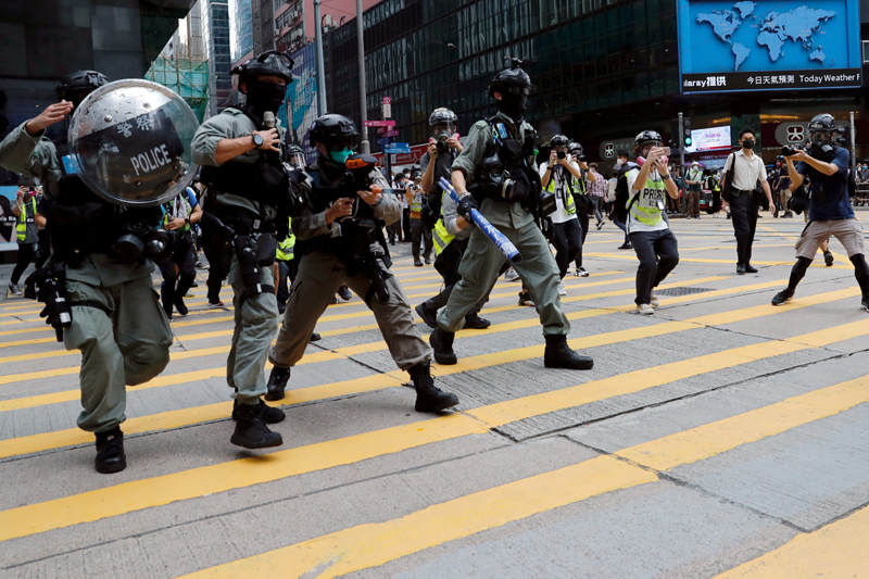 Riot police disperse anti-government demonstrators during a lunch time protest in Central, as a second reading of a controversial national anthem law takes place in Hong Kong, China May 27, 2020. Photo: Reuters