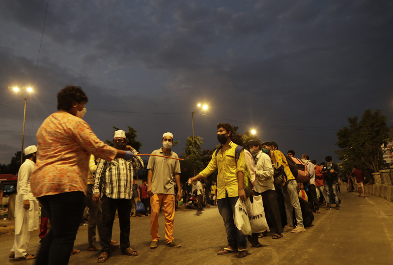 An Indian police officer in plain clothes interacts with the migrant workers from other states before allowing them to  board buses for their onward journey by train to their destination, at Dharavi in Mumbai, India, Friday, May 15, 2020. Photo: AP