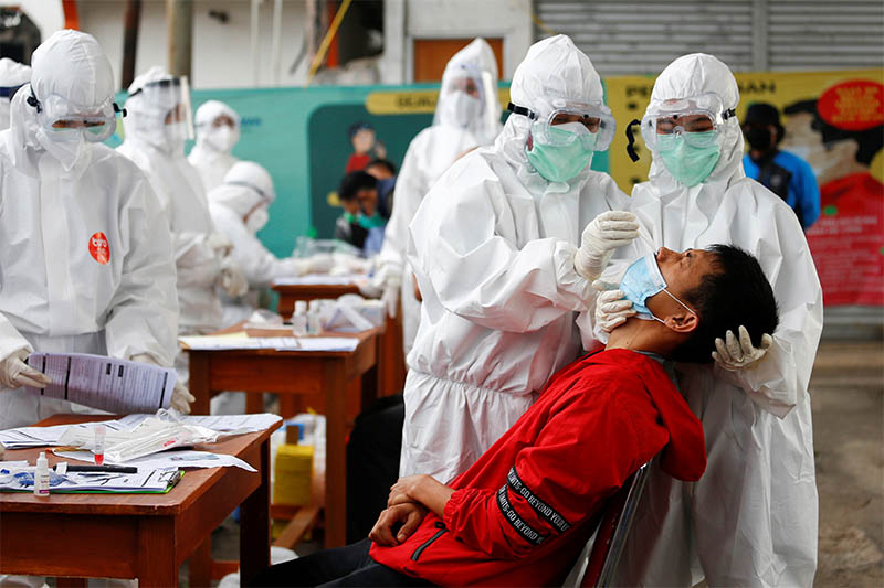 Healthcare workers take a swab sample from a passenger amid the coronavirus disease (COVID-19) outbreak, at a commuter train station in Bogor near Jakarta, Indonesia, May 11, 2020. Photo: Reuters