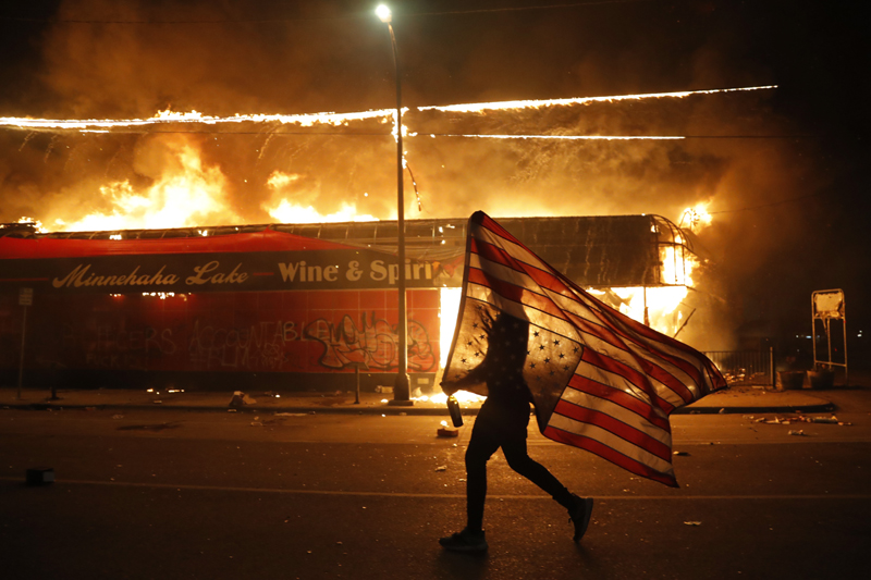 A protester carries a U.S. flag upside down, a sign of distress, next to a burning building Thursday, May 28, 2020, in Minneapolis. Photo: AP