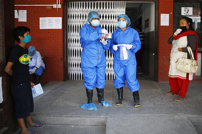 File - Health workers calling out the names of patients after their polymerase chain reaction test turned out to be positive for the novel coronavirus at the National Public Health Laboratory, in Teku, Kathmandu, on Wednesday, May 13, 2020. Photo: Skanda Gautam/THT