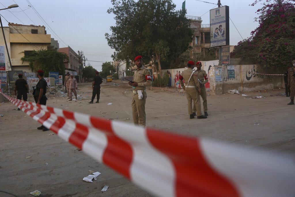 Pakistan army soldiers and police commandos stand guard while they cordon-off a street leading to the site of a plane crash, in Karachi, Pakistan, on Saturday, May 23, 2020. A passenger plane carrying nearly 100 passengers crashed in a crowded neighborhood near the airport in Karachi. Photo: AP