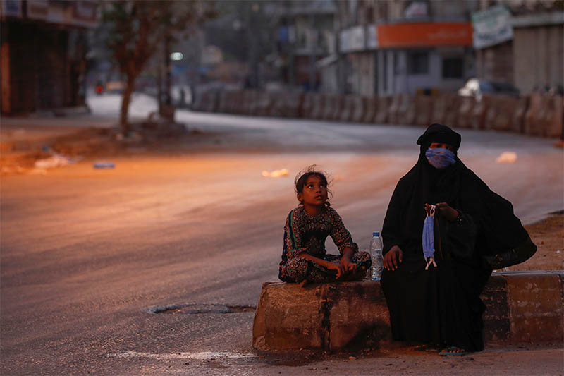 A woman and a girl sit on a deserted road as they sell handmade masks during the Muslim fasting month of Ramadan, amid lockdown in efforts to stem the spread of the coronavirus disease (COVID-19), in Karachi, Pakistan April 28, 2020. Photo: Reuters