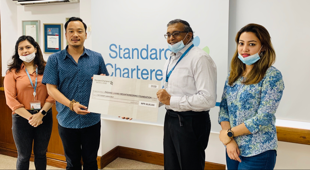 Chief Executive Officer of Standard Chartered Bank Nepal, Anirvan Ghosh Dastidar, hands over a cheque of Rs 5.8 million to Namgyal Sherpa, Vice President (VP) of Pasang Lhamu Mountaineering Foundation. Photo: Standard Chartered Ltd, Nepal