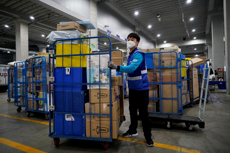 A delivery man for Coupang wearing a mask to prevent contracting the coronavirus, loading packages before leaving to deliver them in Incheon, South Korea, March 3, 2020. Picture taken on March 3, 2020.  Photo: Reuters/File