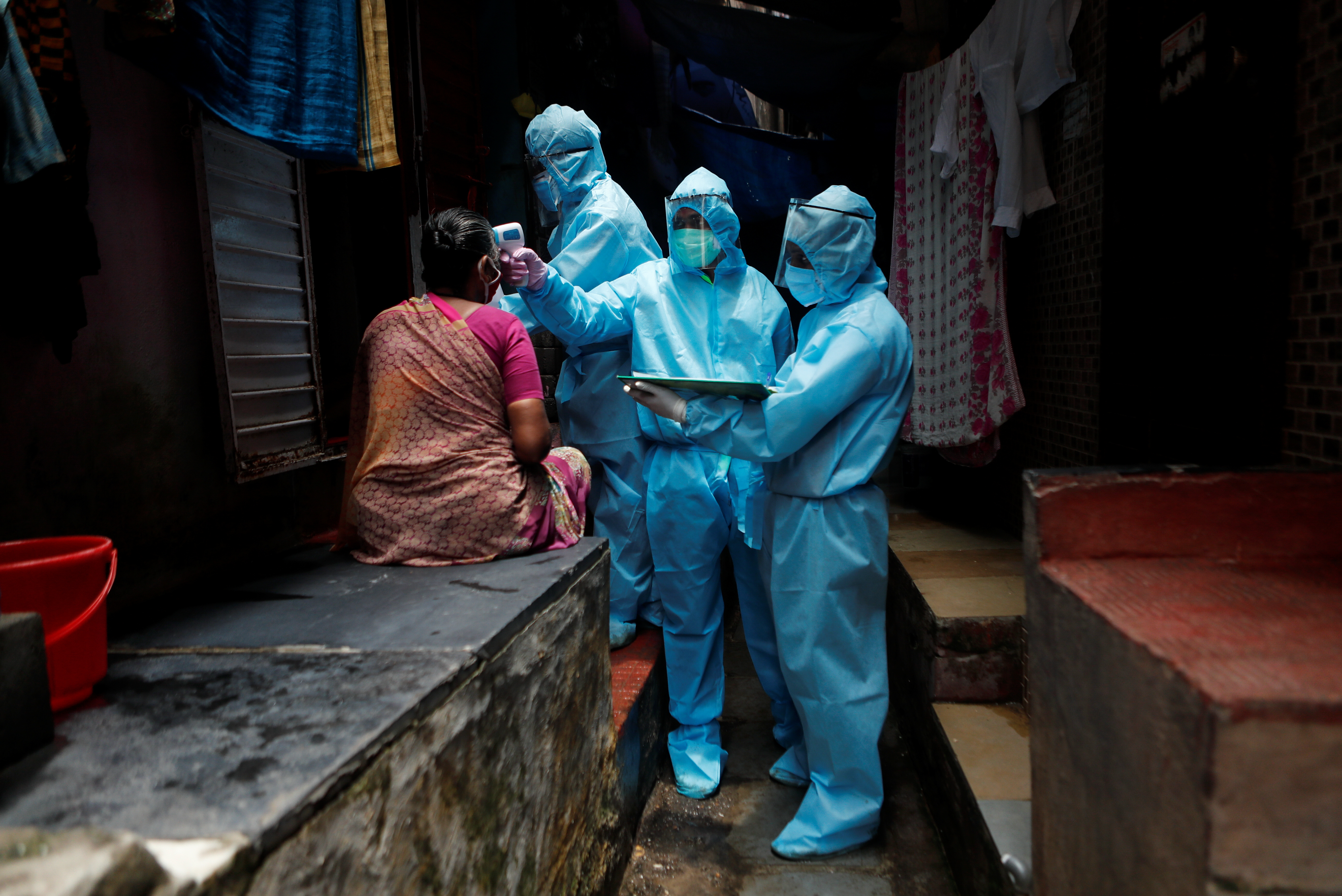 Healthcare workers wearing personal protective equipment (PPE) check the temperature of a resident at a slum during a check-up camp for the coronavirus disease (COVID-19) in Mumbai, India June 14, 2020. Photo: Reuters