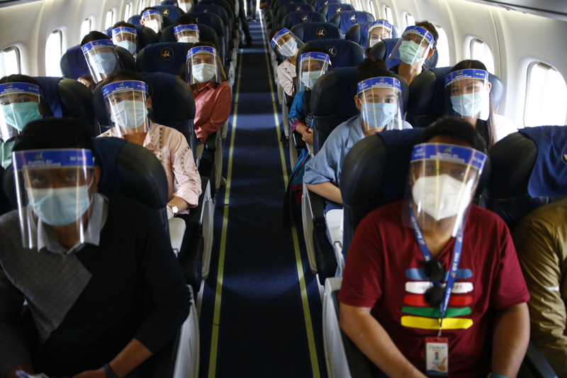 Passengers wearing face masks and face shields look on as the drill unfolds. Photo: Skanda Gautam