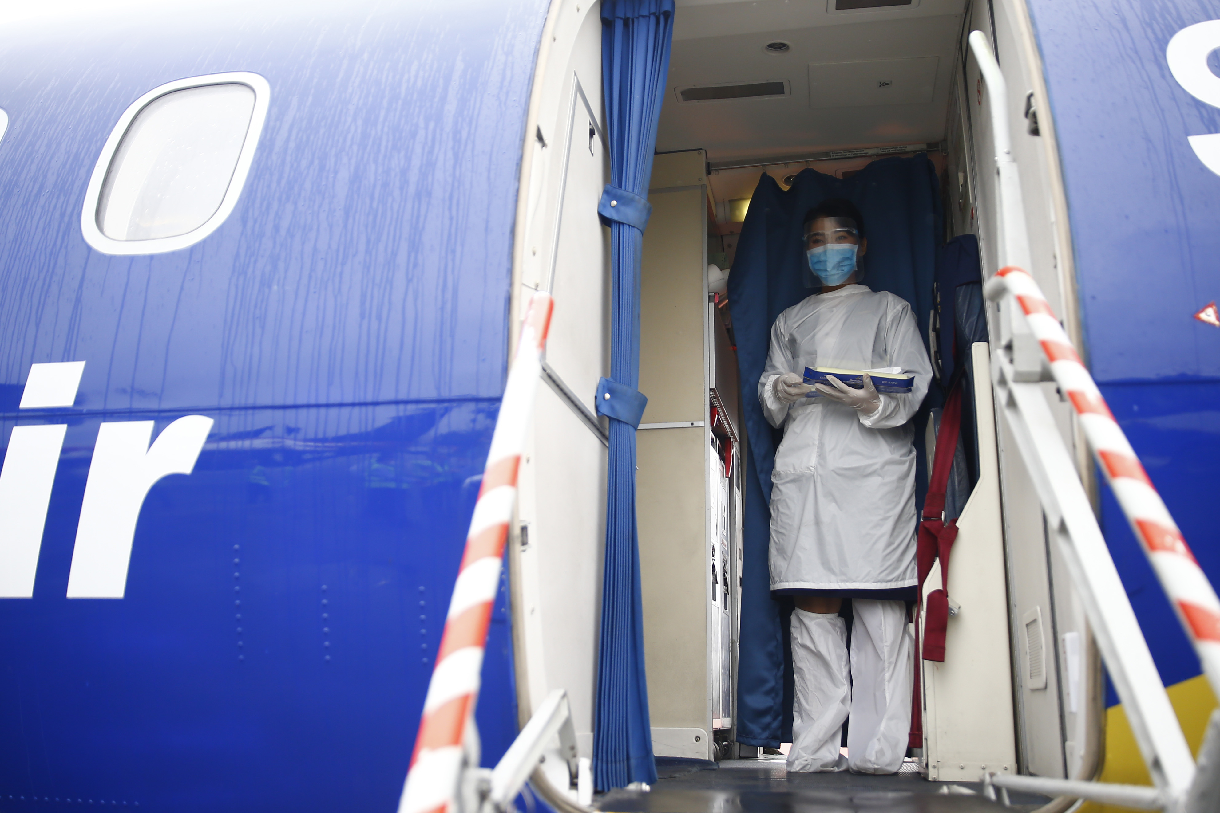 A Buddha Air air-hostess is seen in a protective suit, ready to greet passengers during a mock drill conducted on Thursday at Tribhuvan International Airport to make necessary preparations for the resumption of domestic and international flights, scheduled to start on August 1. Photo: Skanda Gautam/ THT