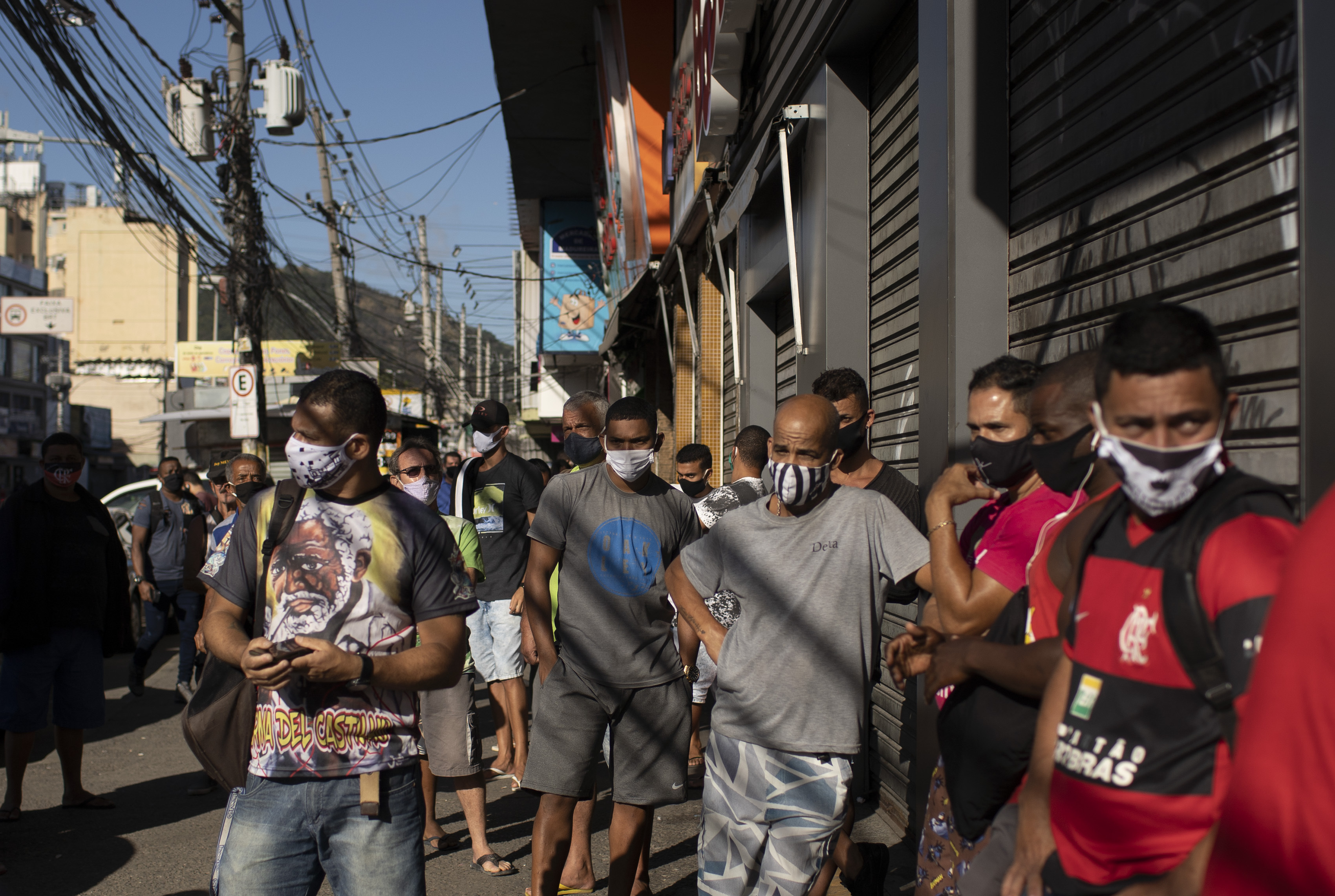 Customers wait to enter the Madureira Market in Rio de Janeiro, Brazil, Wednesday, June 17, 2020. Rio continues with its plan to ease restrictive measures and open the economy to avoid an even worse economic crisis, amid the new coronavirus pandemic. (AP Photo/Silvia Izquierdo)