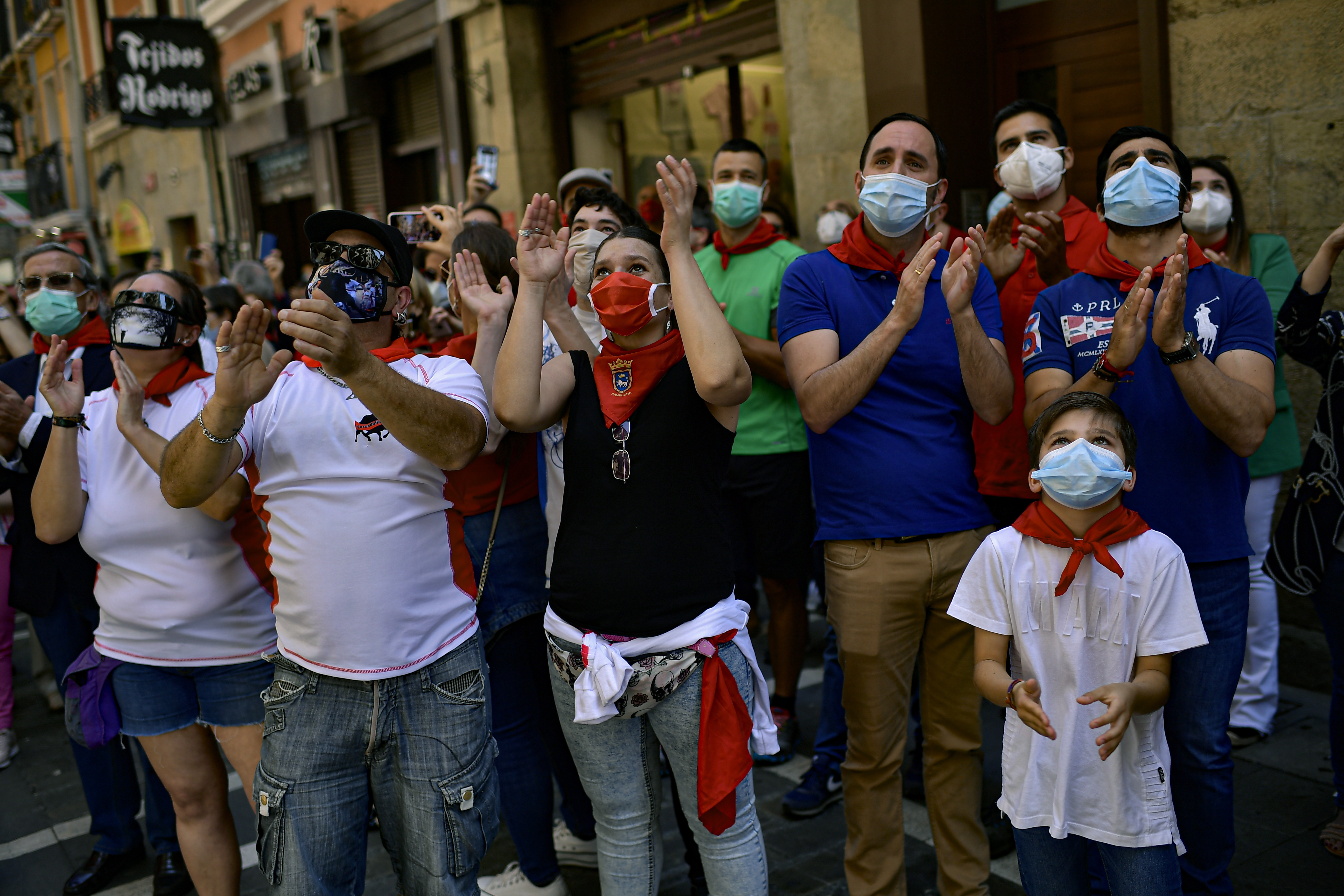 FILE In this Saturday, June 20, 2020 file photo, residents wear faces mask to protect against coronavirus and wear San Fermin's red kerchief as people march the route of the running of the bulls while a singer performs a San Fermin's festival song, in Pamplona, northern Spain. Spain reopened its borders to European tourists Sunday, June 21, 2020 in a bid to kickstart its economy while Brazil and South Africa struggled with rising coronavirus infections. At a campaign rally, President Donald Trump said he told the U.S. government to reduce testing for the virus, apparently to avoid unflattering statistics ahead of the U.S. election in November. (AP Photo/Alvaro Barrientos, File)