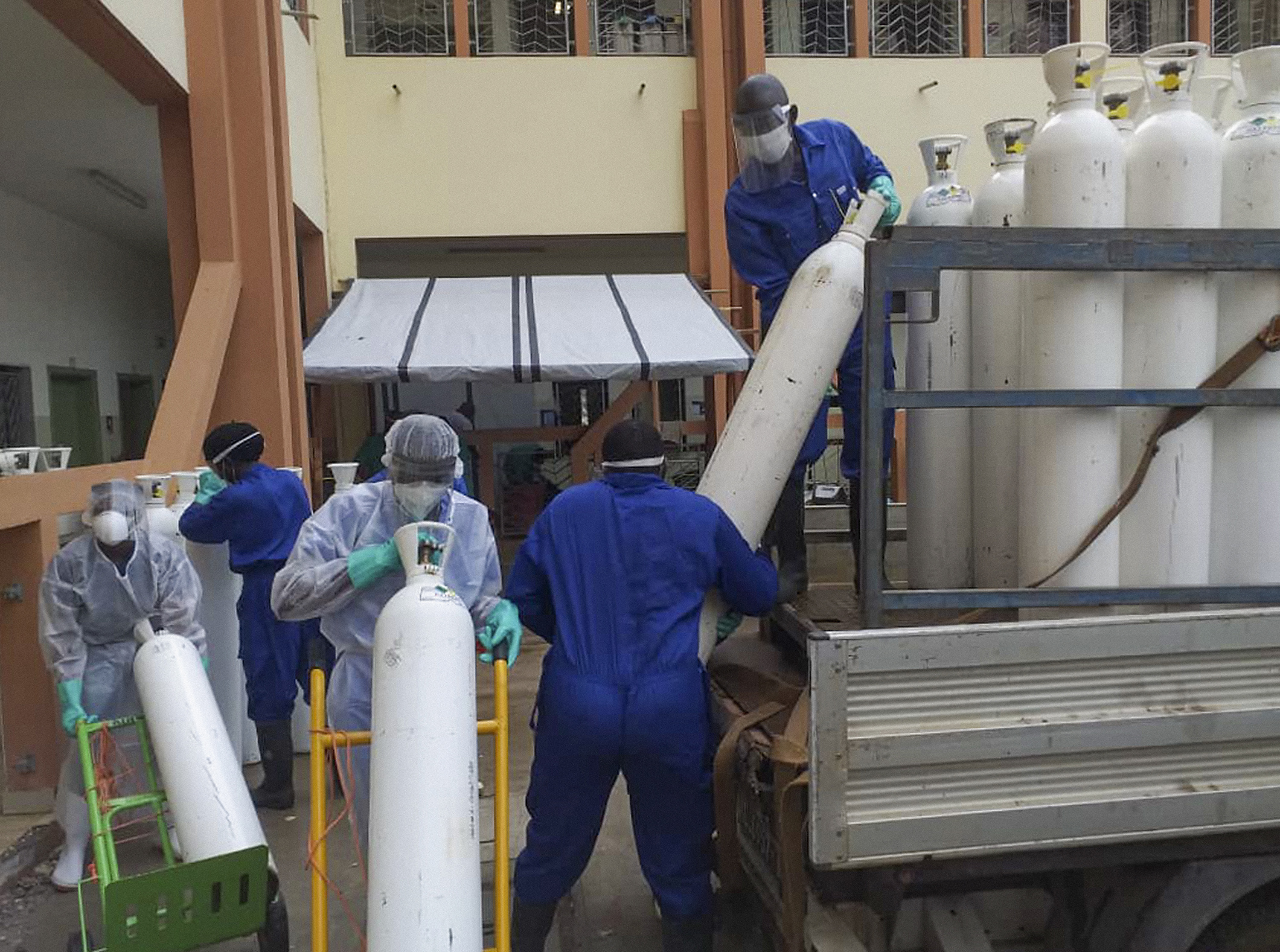 Medical workers offload cylinders of oxygen at the Donka public hospital where coronavirus patients are treated in Conakry, Guinea, on Wednesday, May 20, 2020. Before the coronavirus crisis,u202fthe hospital in the capital was going throughu202f20 oxygen cylinders a day. By May, the hospital was at 40 a day and rising, according to Dr.u202fBillyu202fSivaherau202fofu202fthe aid group Alliance for International Medical Action. Oxygenu202fis the the facility's fastest-growingu202fexpense, and the daily deliveries of cylinders are taking their toll on budgets. Photo: AP