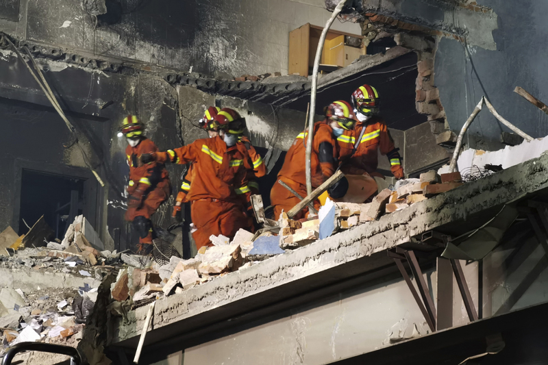 Firefighters look for victims in damaged buildings in the aftermath of a tanker truck explosion near a highway in Wenling in eastern China's Zhejiang province early Sunday, June 14, 2020. More than a dozen were killed and others injured after the tanker truck veered off the Shenyang-Haikou Expressway after the explosion. Photo: Chinatopix via AP
