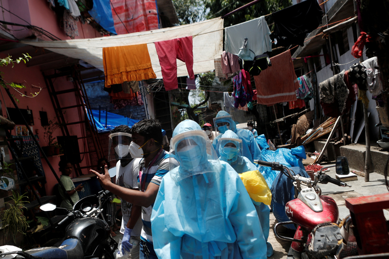 Healthcare workers wearing personal protective equipment (PPE) and volunteers walk through a slum in Dharavi, one of Asia's largest slums, to check residents during a lockdown to slow the spread of the coronavirus disease (COVID-19), in Mumbai, India, June, 7, 2020. Photo: Reuters/File