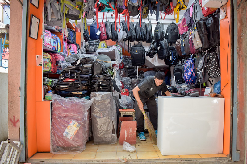 After reopening, a shopkeeper is seen cleaning the store, amid nationwide lockdown, in New Road, Kathmandu, on Thursday, June 04, 2020. Photo: Naresh Shrestha/THT