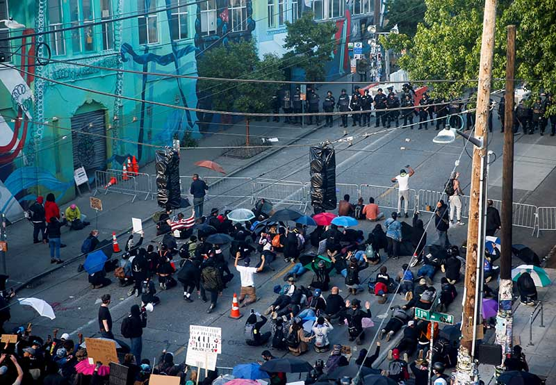 People kneel on the ground after advancing past a police barricade and moving a line of fences up towards a police line during a protest against racial inequality in the aftermath of the death in Minneapolis police custody of George Floyd, near the Seattle Police Department's East Precinct in Seattle, Washington, US, June 7, 2020. Photo: Reuters