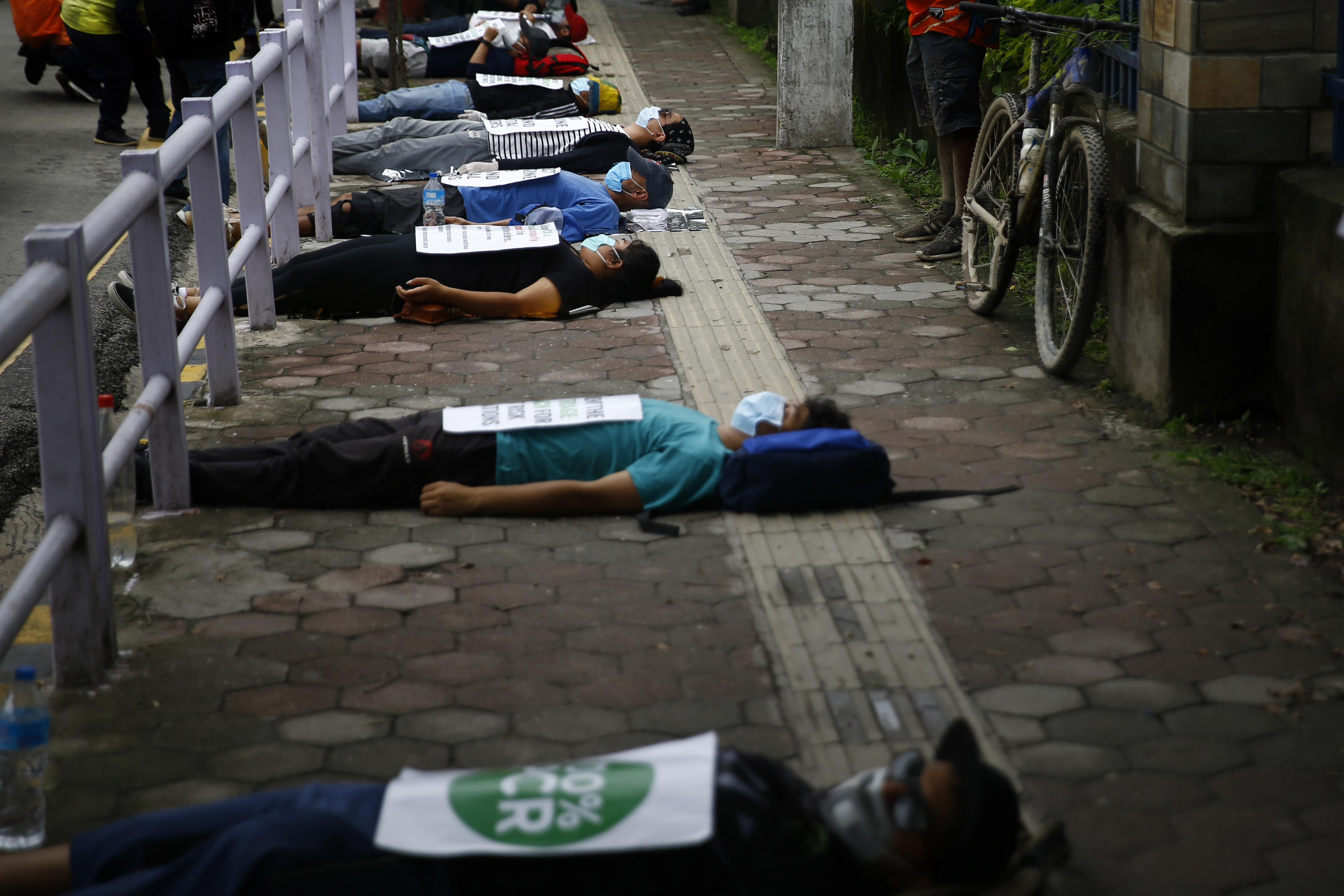 Youths pretend to lay dead on the street during a symbolic protest against the incompetence displayed by the government in dealing with coronavirus crisis, in Kathmandu, on Saturday, June 20, 2020. Photo: Skanda Gautam/THT