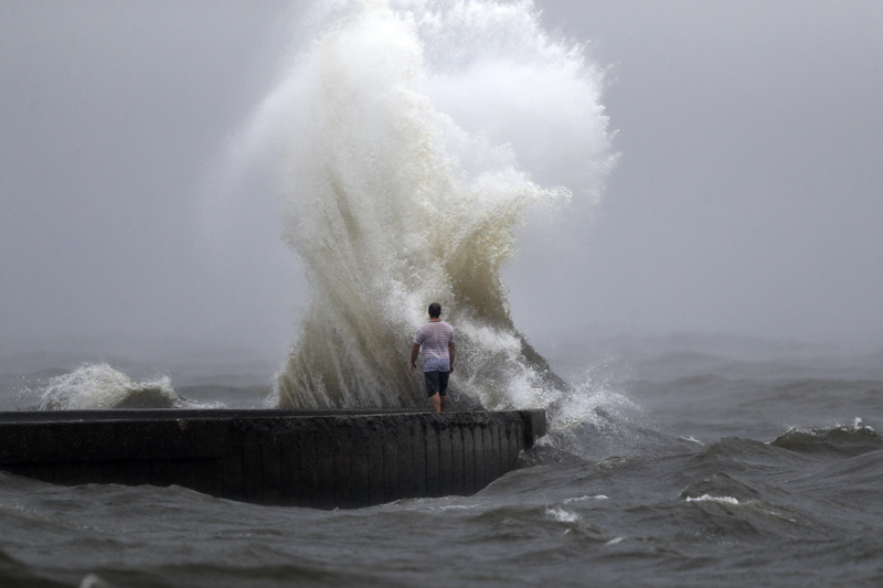 A wave crashes as a man stands on a jetty near Orleans Harbor in Lake Pontchartrain in New Orleans, Sunday, June 7, 2020, as Tropical Storm Cristobal approaches the Louisiana Coast. Photo: AP