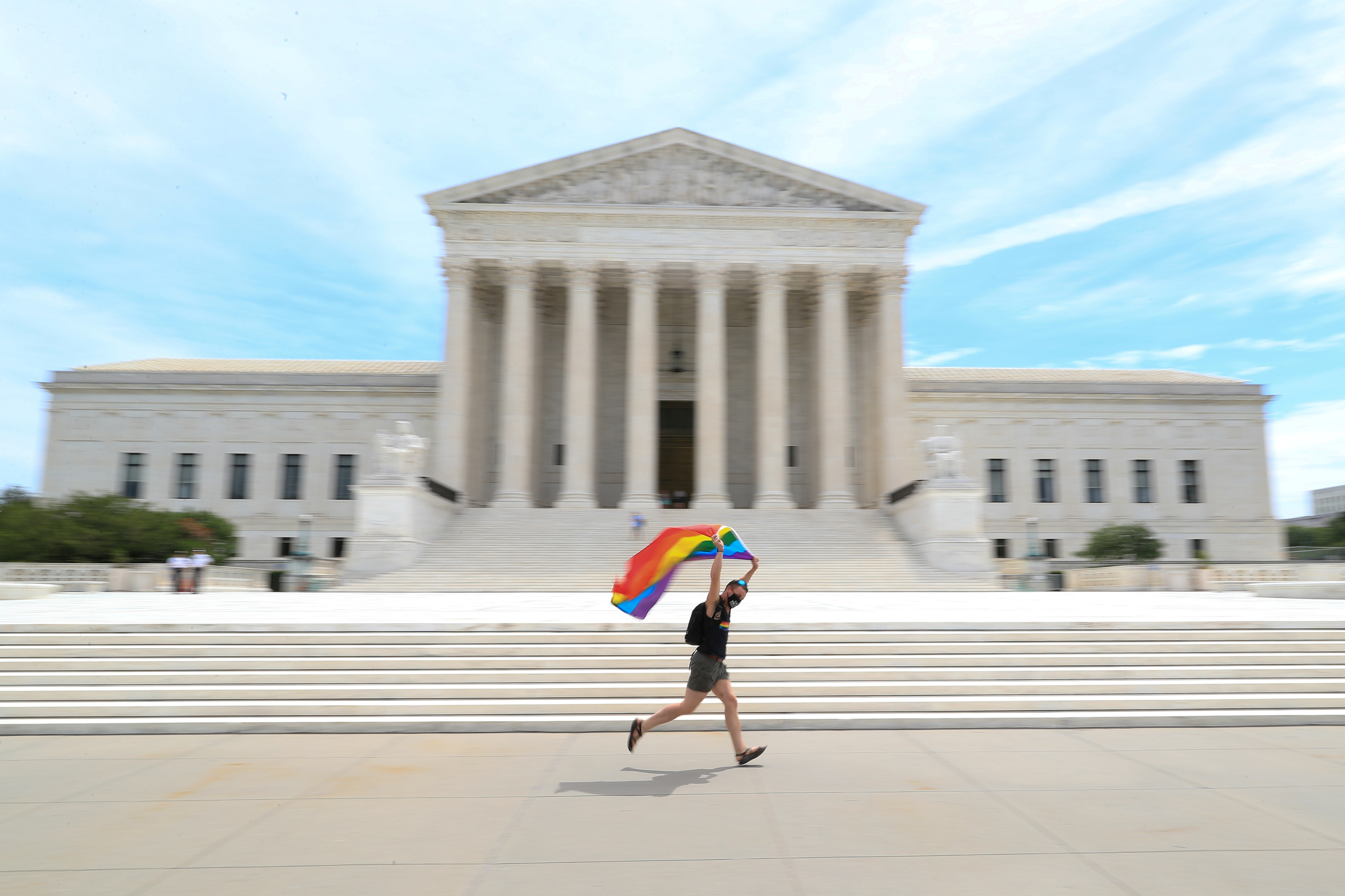 Joseph Fons holding a Pride Flag, runs in front of the US Supreme Court building after the court ruled that a federal law banning workplace discrimination also covers sexual orientation, in Washington, DC, US, June 15, 2020.  Photo: Reuters