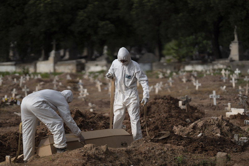 Cemetery workers in protective clothing maneuver the coffin of 57-year-old Paulo Jose da Silva, who died from the new coronavirus, in Rio de Janeiro, Brazil, Friday, June 5, 2020. Photo: AP