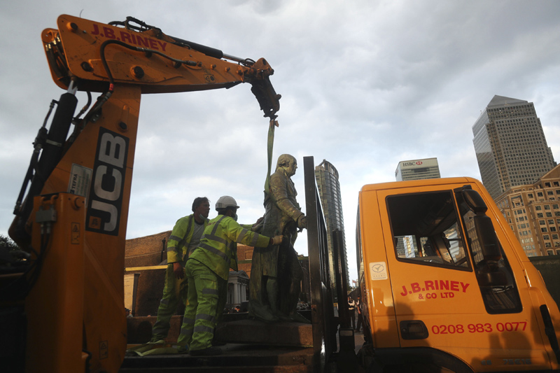 Workers transport a statue of slave owner Robert Milligan which was taken down, in West India Quay, east London, Tuesday, June 9, 2020, after a protest saw anti-racism campaigners tear down a statue of a slave trader in Bristol. London's mayor says statues of imperialist figures could be removed from the city's streets, in the latest sign of change sparked by the death of George Floyd. London Mayor Sadiq Khan says he is setting up a commission to ensure monuments reflect the city's diversity. Photo: Yui Mok/PA via AP