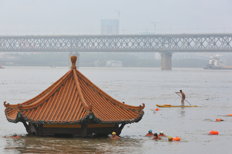 People swim near a pavilion partially submerged in floodwaters on the banks of the Yangtze River, following heavy rainfall in Wuhan, Hubei province, China July 8, 2020. China Daily via Reuters/File