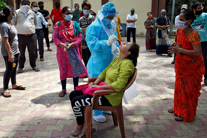 A healthcare worker wearing Personal Protective Equipment (PPE) takes swab from a woman to test for the coronavirus disease (COVID-19) at a residential area in Ahmedabad, India, on July 8, 2020. Photo: Reuters