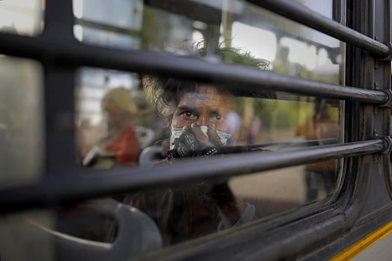 An Indian homeless man sits in a bus as he is being evicted with other homeless people and migrant laborers from the banks of Yamuna River where they have been squatting during the coronavirus lockdown in New Delhi, India, April 15, 2020. Photo: AP/File