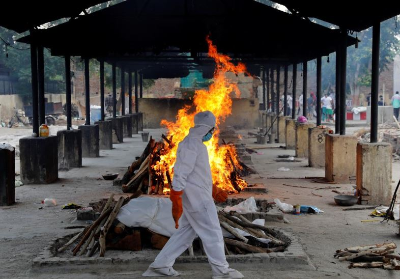 A priest wearing personal protective equipment (PPE) walks in front of the body of a person who died of the coronavirus disease (COVID-19), as he collects woods to make a funeral pyre at a crematorium in New Delhi, India, July 3, 2020.  Photo: Reuters