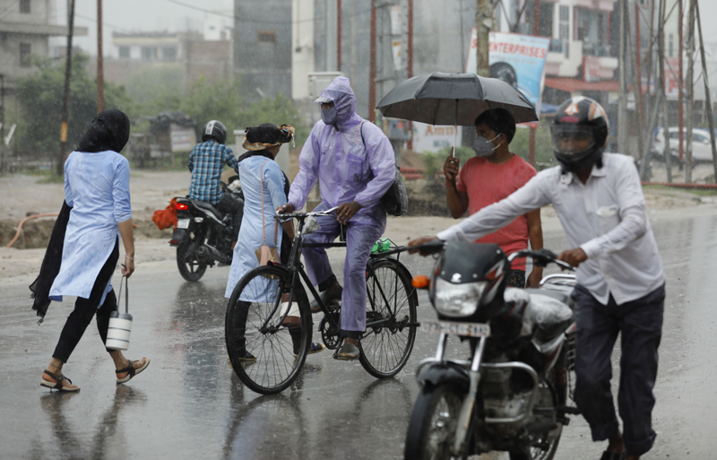 People wear face masks and move through a street in the rain in Prayagraj, India, Wednesday, July 29, 2020. Photo: AP
