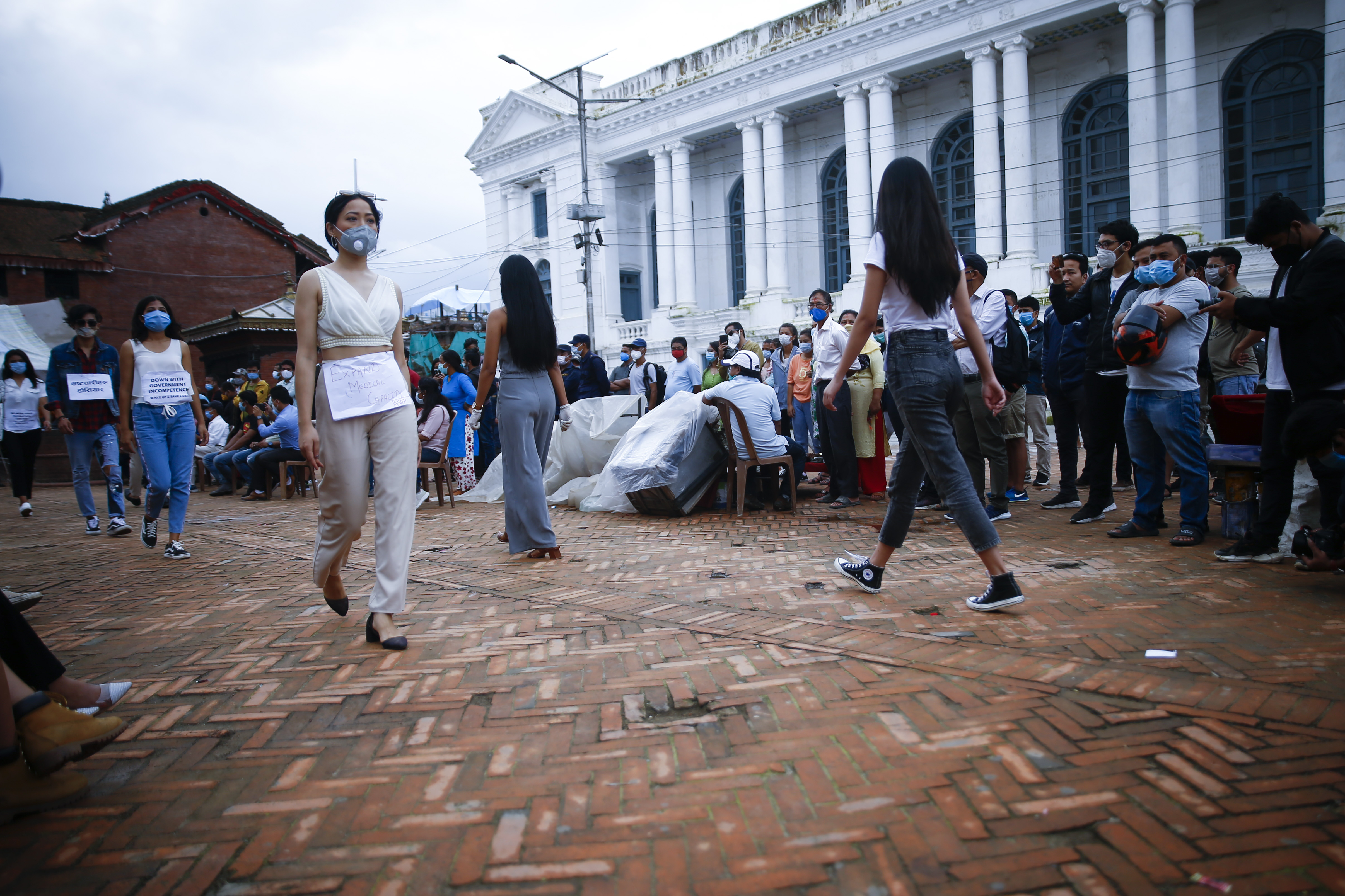 People walk in Basantapur Durbar Square courtyard to express solidarity for the youths who are on their 11th day of hunger strike as part of a protest to hold concerned authorities accountable for better COVID-19 response, in Kathmandu, on Tuesday, July 28, 2020. Photo: Skanda Gautam/THT