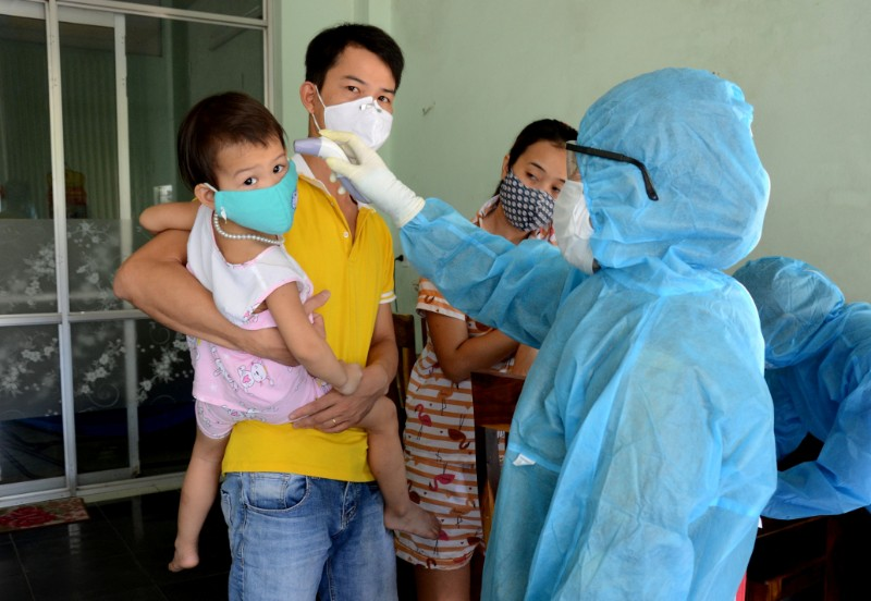 A health worker gets the temperature of residents at the area of a newly found coronavirus infected patient in Da Nang city, Vietnam July 26, 2020. Photo: Quoc Dung/VNA via Reuters
