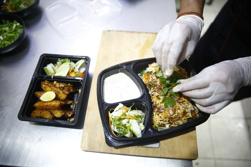 Take-away meals being prepared at H20 Café and Pub in Chabahil on Sunday. The government has expedited action against restaurants failing to comply with recent regulations according to which. eateries can offer only take-away services and disallow gathering of people. Photo: Skanda Gautam/ THT