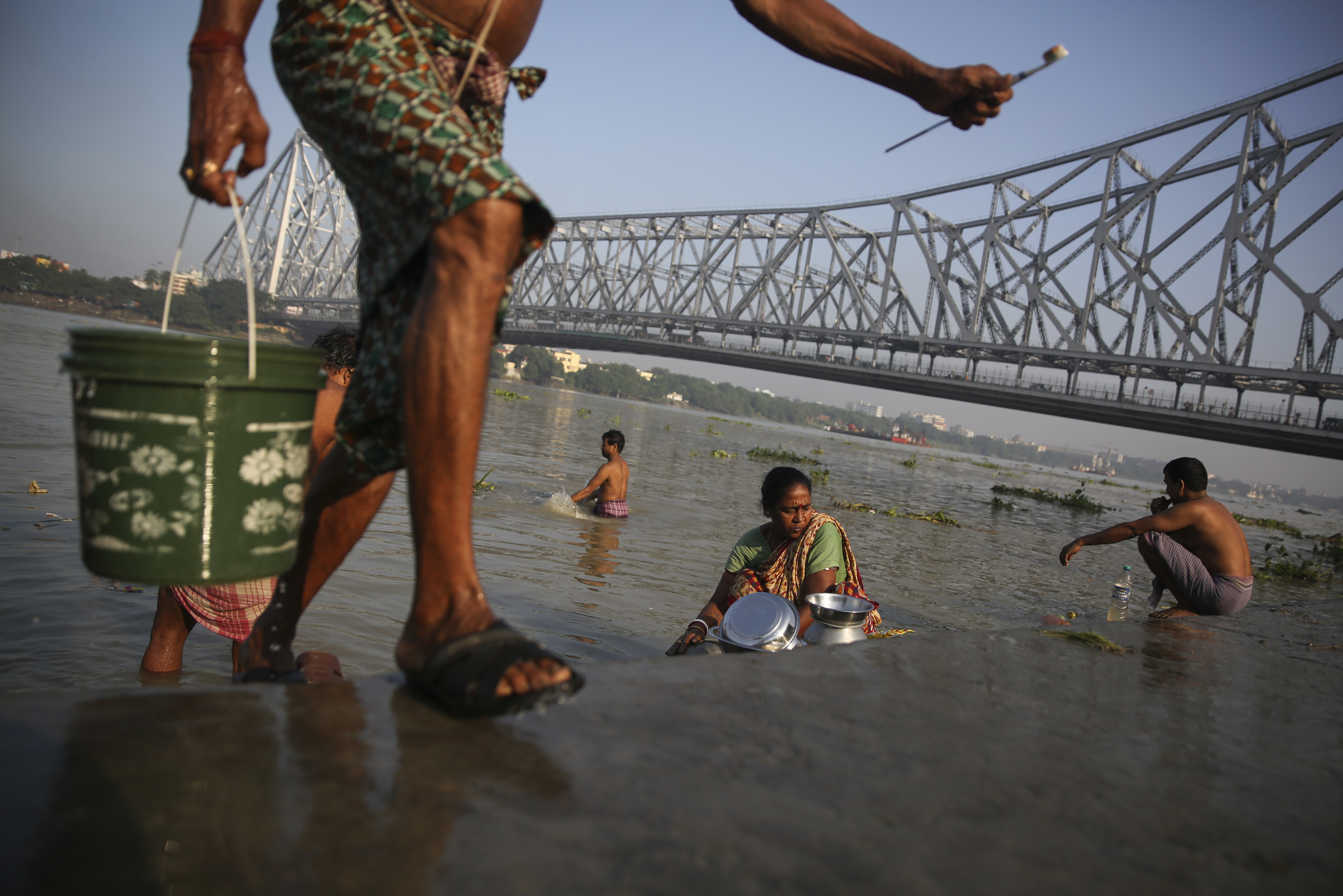 A man carries a bucket of water while people wash utensils, brush their teeth and bathe in the polluted waters of the river Hooghly, a distributary of the river Ganges and known as Ganga by locals, in the backdrop of the landmark Howrah Bridge in Kolkata, in the eastern Indian state of West Bengal, Friday, October 11, 2019. Once the capital of the British raj, today the seething metropolis is home to nearly 15 million people. (AP Photo/Altaf Qadri)