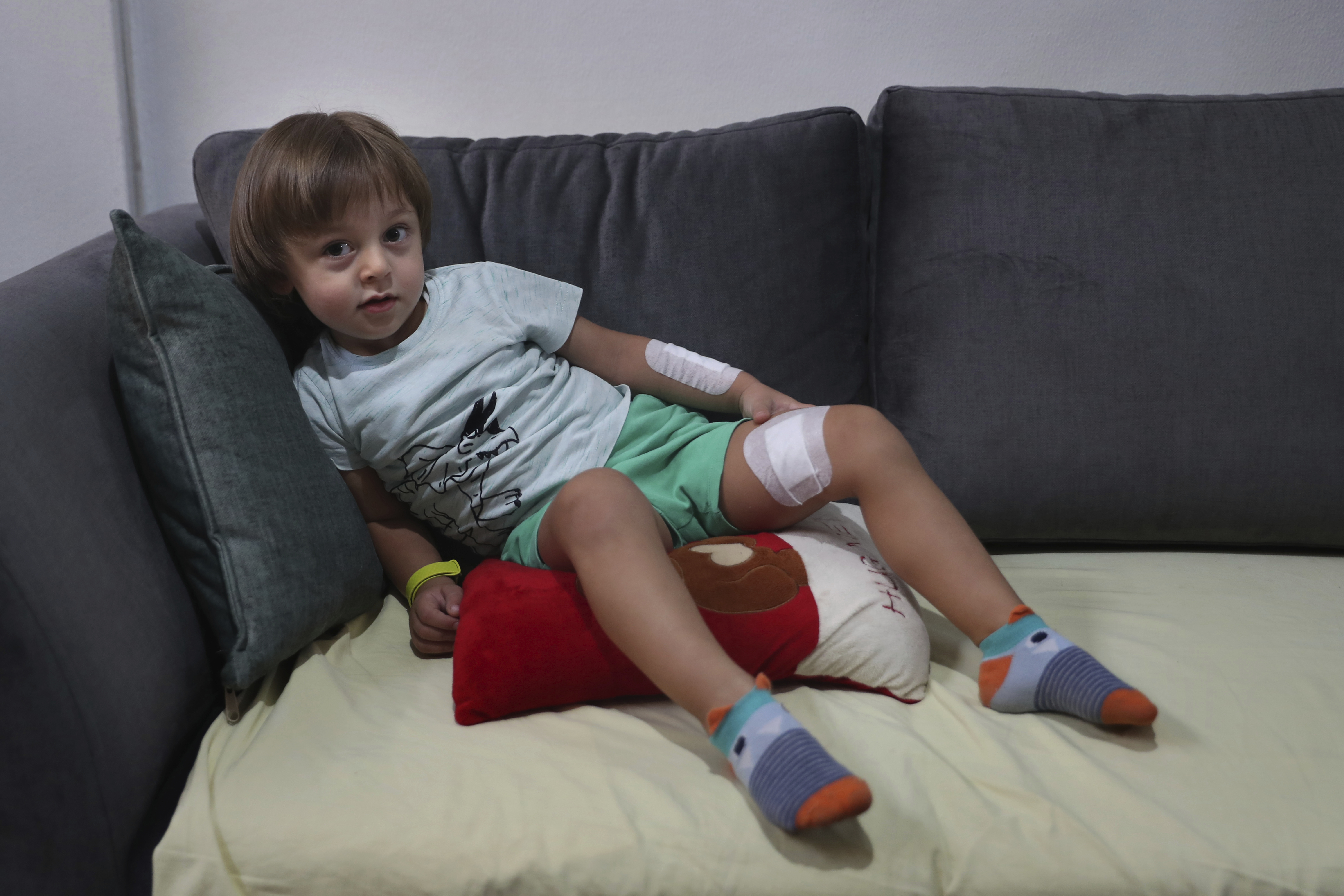 Three-year-old Abed Achi lies on a sofa at his family house in Beirut, Lebanon, Tuesday, Aug. 11, 2020. Abed was playing with his Lego blocks when the huge blast ripped through Beirut, shattering the nearby glass doors. He had cuts on his tiny arms and feet, a head injury, and was taken to the emergency room, where he sat amid other bleeding people. Photo: AP