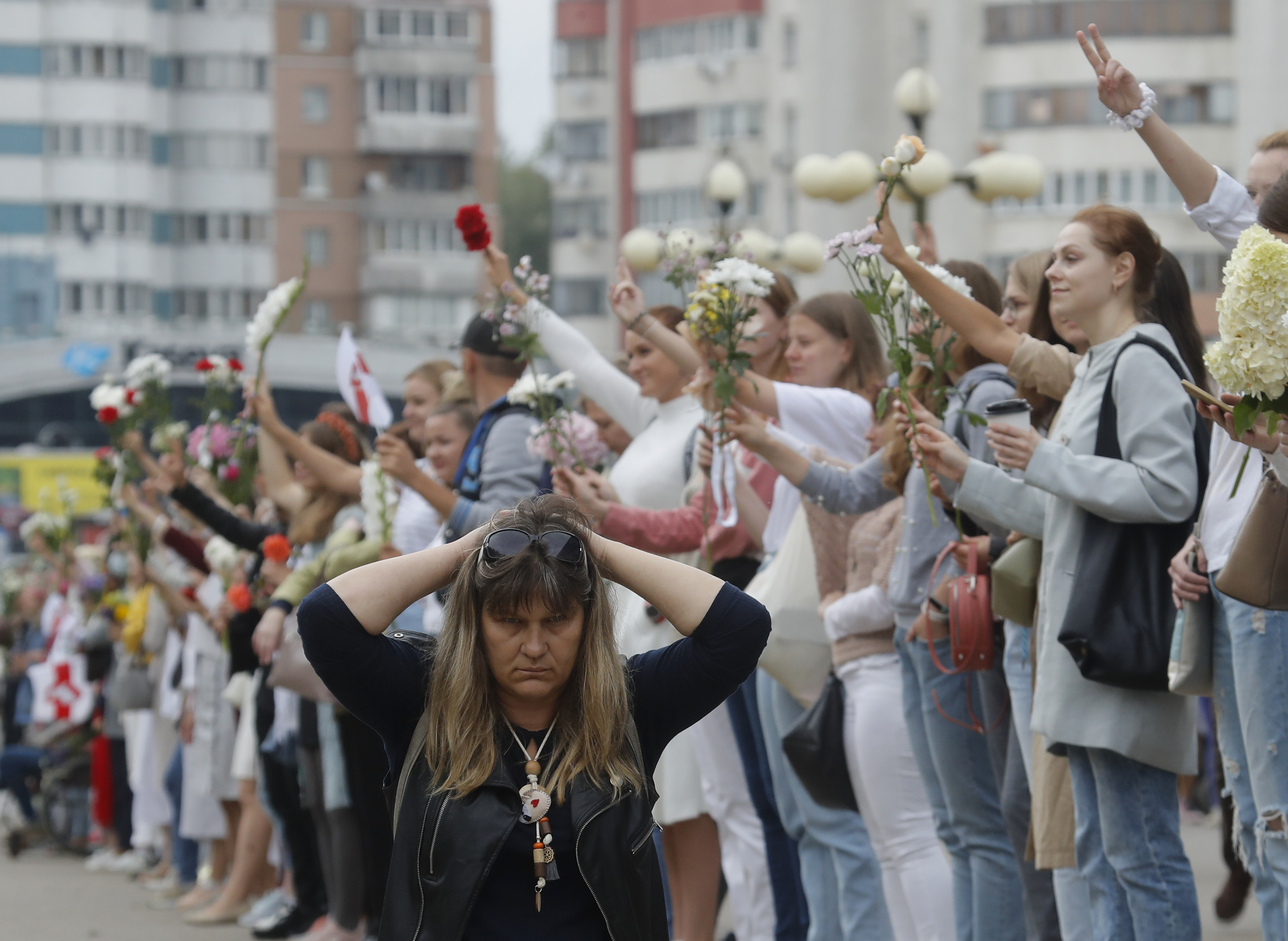 A woman kneels on the ground as people create a human chain during a protest in Minsk, Belarus, Saturday, Aug. 22, 2020. Demonstrators are taking to the streets of the Belarusian capital and other cities, keeping up their push for the resignation of the nation's authoritarian leader. President Alexander Lukashenko has extended his 26-year rule in a vote the opposition saw as rigged. Photo: AP