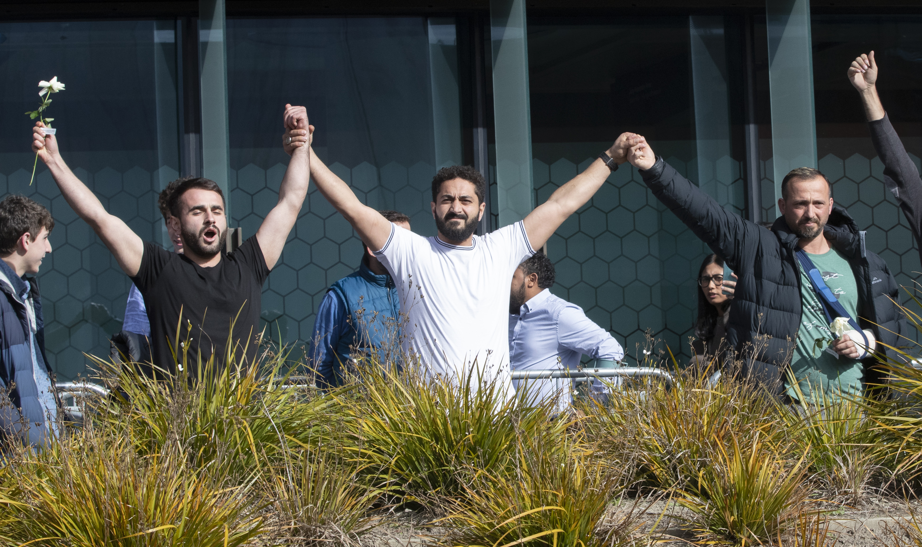 Mosque shooting survivors from left, Mustafa Boztas, Wassail Daragmih and Temel Atacocugu celebrate as they leave the Christchurch High Court after the sentencing hearing for Australian Brenton Harrison Tarrant, in Christchurch, New Zealand, Thursday, Aug. 27, 2020. Tarrant, a white supremacist who killed 51 worshippers at two New Zealand mosques in March 2019 was sentenced to life in prison without the possibility of parole. Photo: AP