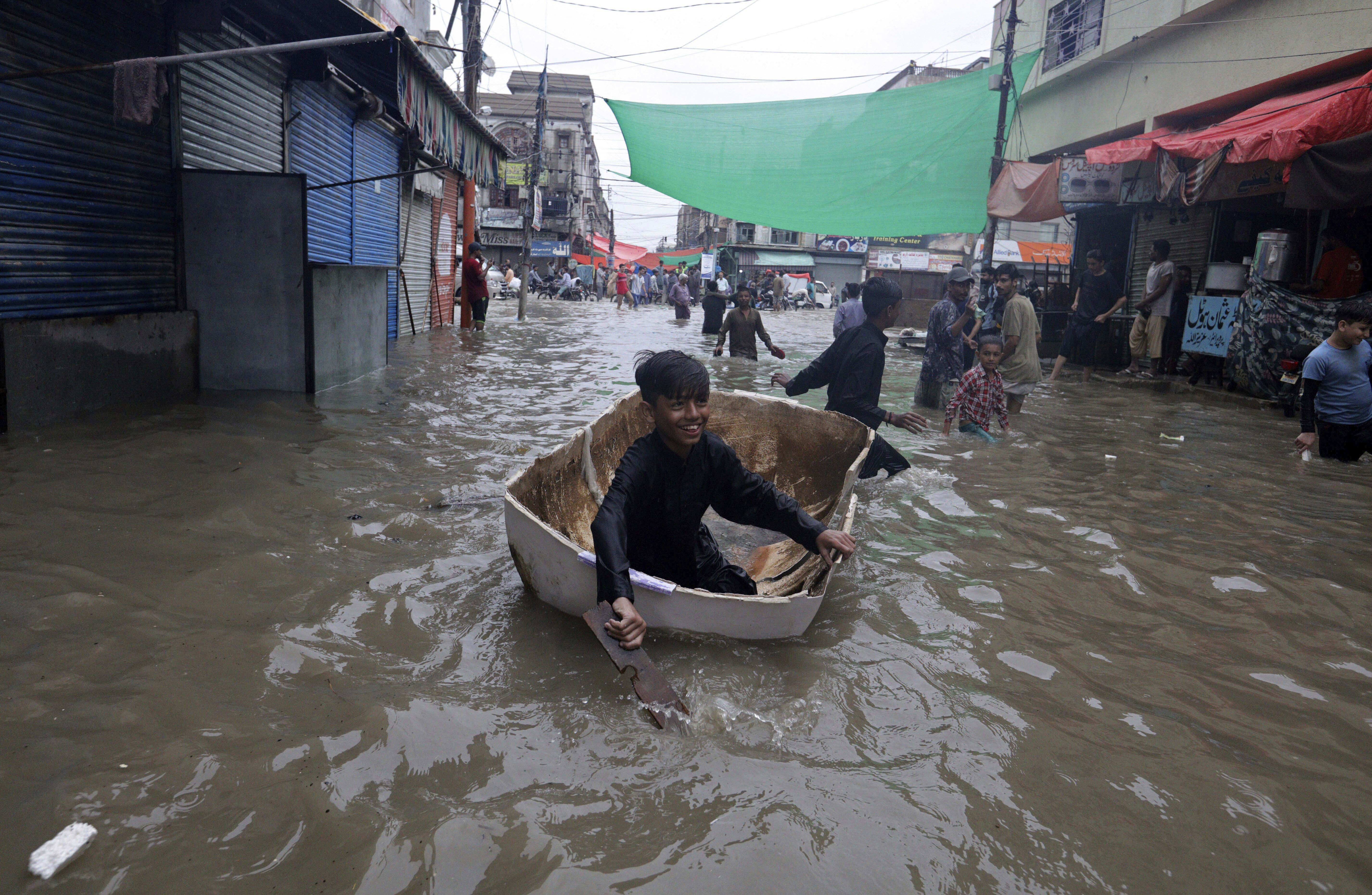 A boy uses half of a fiber tank to navigate a flooded street after heavy monsoon rains, in Karachi, Pakistan, Thursday, Aug. 27, 2020. Heavy monsoon rains have lashed many parts of Pakistan as well the southern port city of Karachi, leaving flooding streets, damaging homes and displacing scores of people. (AP Photo/Fareed Khan)
