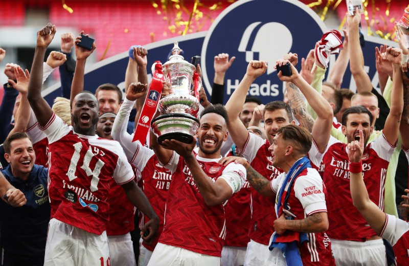 Arsenal's Pierre-Emerick Aubameyang celebrates with the trophy and teammates after winning the FA Cup, as play resumes behind closed doors following the outbreak of the coronavirus disease (COVID-19). Photo:  Pool via Reuters