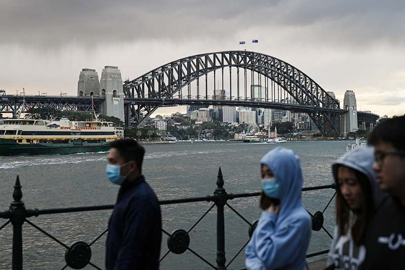 People walk in front of the Sydney Harbour Bridge as the state of New South Wales continues to report low numbers for new daily cases of the coronavirus disease (COVID-19) in Sydney, Australia, on August 19, 2020. Photo: Reuters