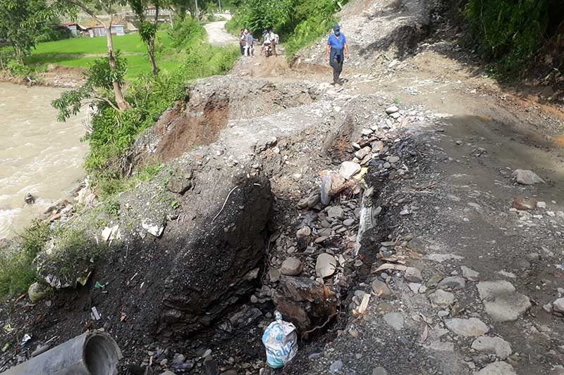 Local residents are seen using a road damaged by rain-triggered landslide and flood, on the bank of Thopal River in Nilkantha Municipality-12, Dhading district, on Monday, August 10, 2020. Photo: Keshav Ashikari/THT